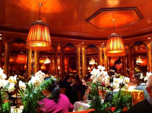 Interior of cafe, with flowers, mirrors, warm festive feel